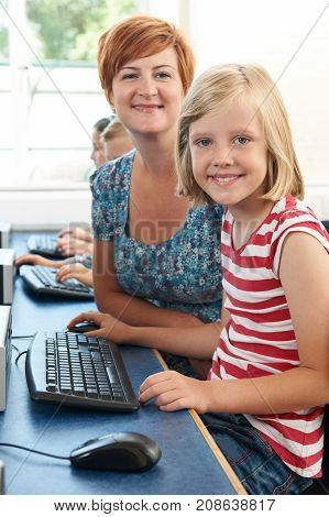 Portrait Of Female Elementary Pupil In Computer Class With Teacher