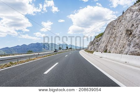 High-speed country road among the mountains on a summer day.