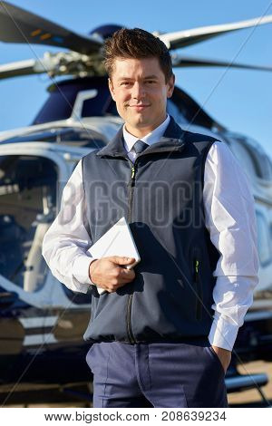 Portrait Of Pilot Standing In Front Of Helicopter With Digital Tablet