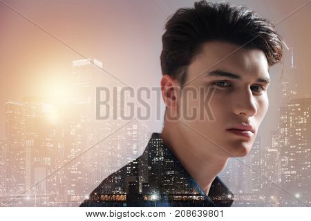 Bright city. Close up of pleasant teenager standing in front of you while expressing calmness and peace