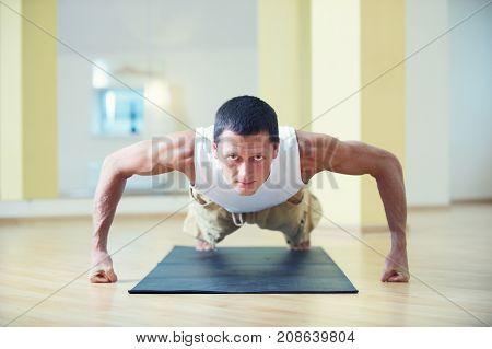 A young strong man doing yoga exercises - Chaturanga Dandasana four limbed staff pose in the yoga studio.
