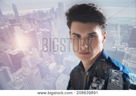 City rush. Close up of handsome lovely teenager standing against city background while having pleasant mood