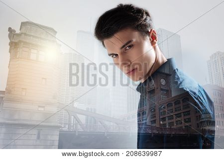 City life. Close up of young charismatic model standing in urban surrounding while expressing calmness