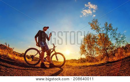 Oung Athletic Guy In A Black T-shirt, Blue Jeans Shorts And Knee Pads On A Sports Bike