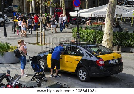 Barcelona Catalonia Spain - JUNE 9 2017 :Tourist visiting Barcelona takes a taxi in the historic center of city.