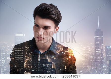 Beautiful night city. Charismatic teenager looking away while standing against wonderful city lights