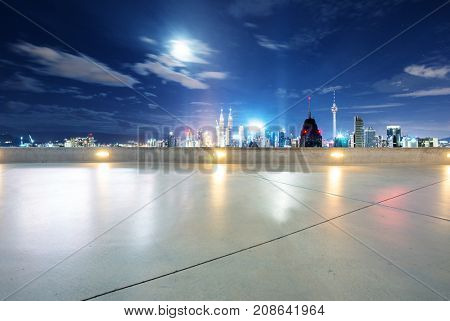 empty marble floor and cityscape of kuala lumpur in blue cloud sky at night