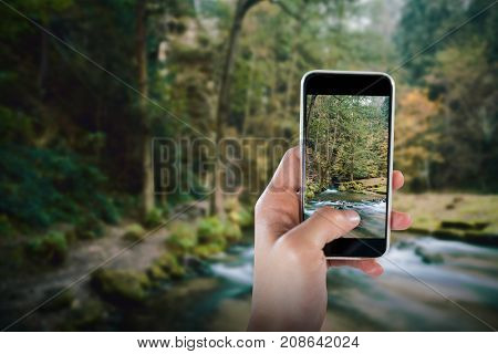 Cropped image of hand holding smart phone against rapids flowing along lush forest