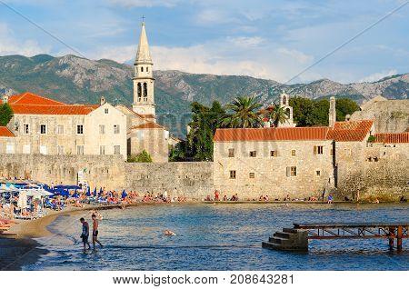 BUDVA MONTENEGRO - SEPTEMBER 5 2017: Unknown people rest on beach near Old Town in popular resort of Budva Montenegro