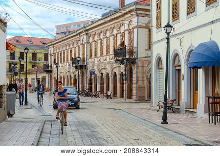 SHKODER ALBANIA - SEPTEMBER 6 2017: Unknown people ride bicycles and walk along street (Rruga G'juhadol) in center of Shkoder Albania