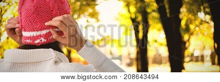 Rear view of woman in knit hat against defocused image of trees growing at park
