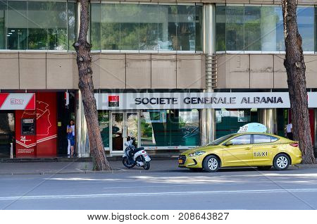 TIRANA ALBANIA - SEPTEMBER 6 2017: Taxi on Boulevard of Martyrs near complex of buildings Tirana Twin Towers Tirana Albania. Unknown people walking down street