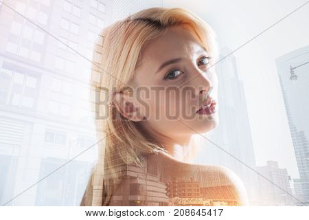 Fast life tempo. Close up of good looking girl expressing calmness in her eyes while standing in urban surrounding