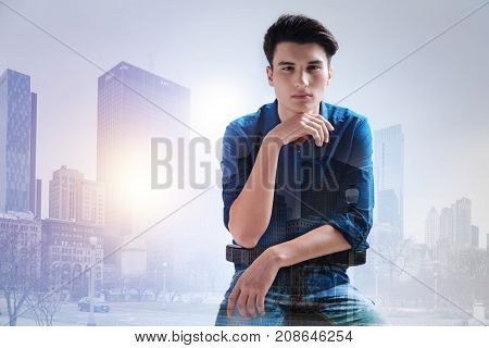 Foggy morning. Waist up of thoughtful teenager keeping his hand under the chin while sitting against urban background