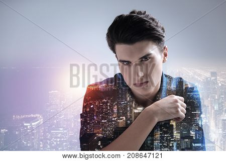 Slightly disappointed. Close up of handsome model having shrewd glance while standing against night city