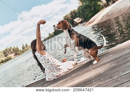 Always together. Rear view of cute little girl playing with her dog while sitting near the lake outdoors