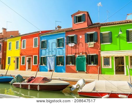 Colorful houses and boats on channels of Burano Island. Venice, Italy