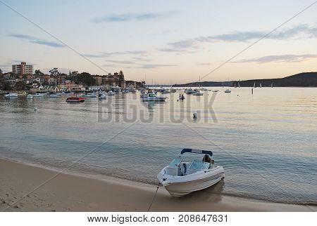 Private boat on the beach at Manly Cove during pink sunset. Sydney NSW Australia.