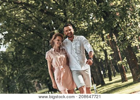Real love. Beautiful young couple bonding and smiling while walking in the park together