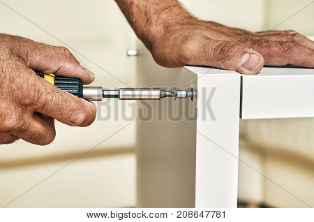 Male hands assembling furniture at home close-up