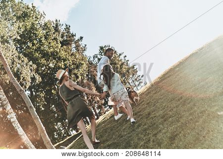 Nothing but family. Full length rear view of young family of three holding hands while running outdoors