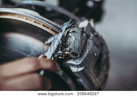 Cropped image of mechanic is working in auto service. Car repair and maintenance. Measuring the thickness of brake disc to identify its run-out.
