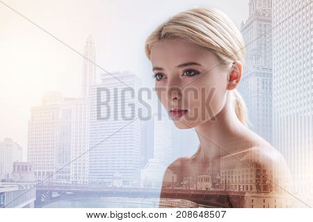 Dragging attention. Close up of concentrated girl looking at the distance while standing against urban background