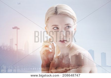 Weekend time. Lovely girl having expressing calmness while looking away and standing in urban surrounding