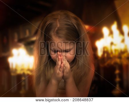 Beautiful little girl folded her hands in a prayerful gesture. Child praying in the temple