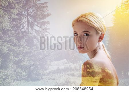 Fine day. Close up of adorable girl looking at you and expressing calmness while standing against nature background