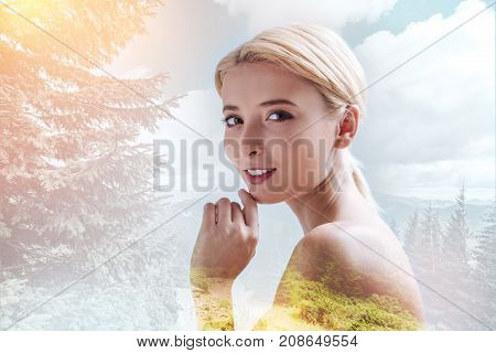 Pleasant smile. Charming girl expressing optimism while touching her chin and standing against nature background