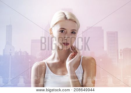 Morning city. Close up of adorable girl touching her face with a hand while showing calmness on her face