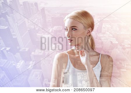 Looking cute. Pleasant model expressing calmness and looking away while standing in urban surrounding