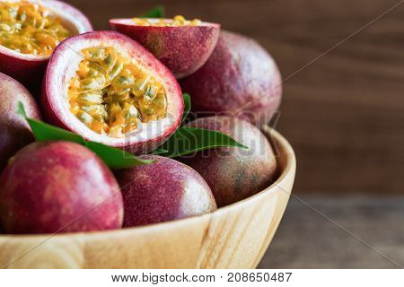Close up fresh passion fruit in wood bowl on wood table in side view with copy space for background or wallpaper. Ripe passion fruit so delicious sweet and sour. Passion fruit is tropical fruit. Macro concept of fresh passion fruit.