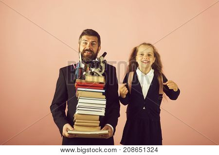 Father and schoolgirl with happy faces on pink background. Home schooling and back to school concept. Kid and dad hold pile of books and stationery. Girl in school uniform and man with beard