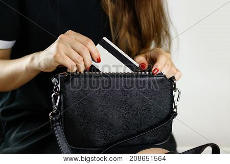 Girl In Black Dress Pulls Out Credit Card From A Black Purse. Closeup