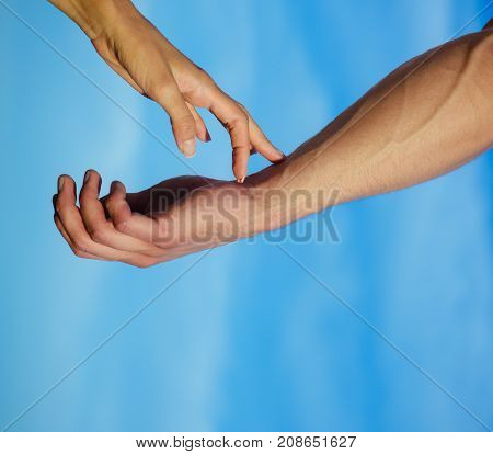 Female fingers touching male arm skin with veins. Two hands on cloudy blue sky. Communication and connection. Tenderness love and care concept. Partnership and friendship.
