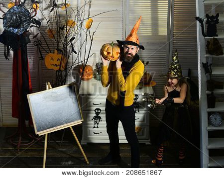 Girl Witch And Bearded Wizard Hold Pumpkin And Candlestick