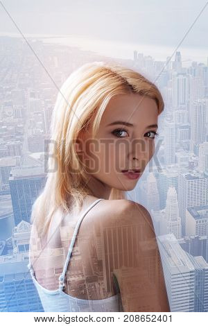 Outstanding look. Close up of beautiful girl expressing calmness while looking at you and standing against city background