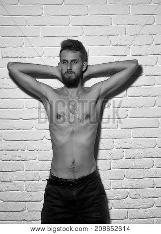 Slim Bearded Man With Thin Bare Torso On Brick Background