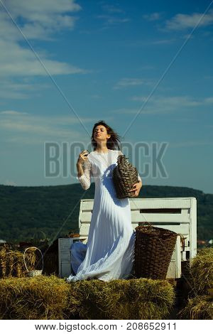 Girl in white dress posing on blue sky. Model with alcohol drink on sunny day. Woman with glass of wine wicker bottle and basket. Winery tour concept. Summer vacation holidays and celebration.
