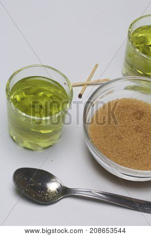 Absinthe Of Green Color Is Poured Over Glasses. Brown Sugar For Caramelization Of A Drink And Matche