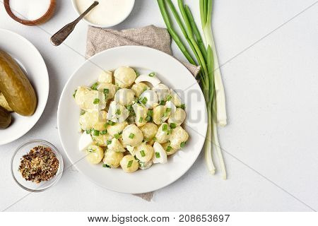 Traditional german potato salad with eggs and green onion dressing with yoghurt and mayonnaise on white stone background with copy space top view