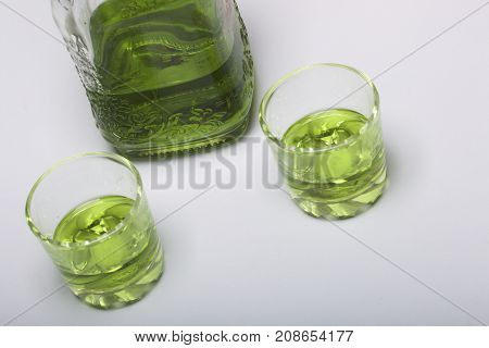 Absinthe Is Green. In A Bottle And Poured Into Glasses. On A White Table-top.