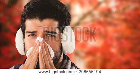 Close-up portrait of man blowing nose with tissue paper against low angle view of autumn maple tree