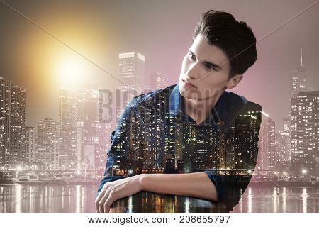 Evening city. Close up of cute teenager relaxing outdoors while looking at the distance and expressing calmness