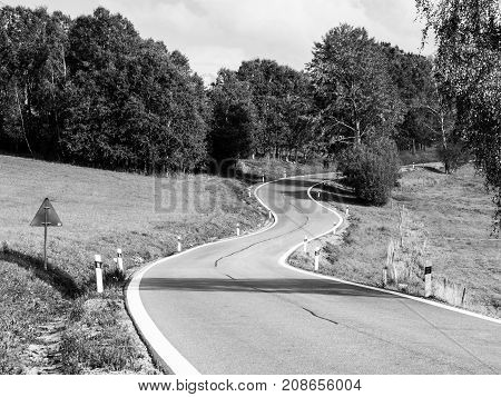 Winding asphalt road in rural landscape of Sumava Mountains, Czech Republic. Black and white image.