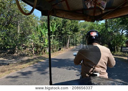 A Tricycle Driver Carrying Some Tourists Around Angkor Wat And Siem Reap