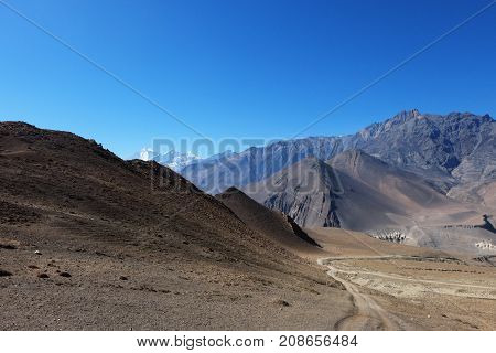 Mountain road in the Himalayas at an altitude of 4500 meters with a mountain nilgiri in the background.
