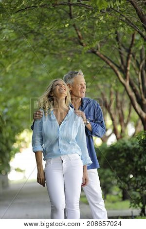 Attractive Mature Couple Posing On A Green Tree Background